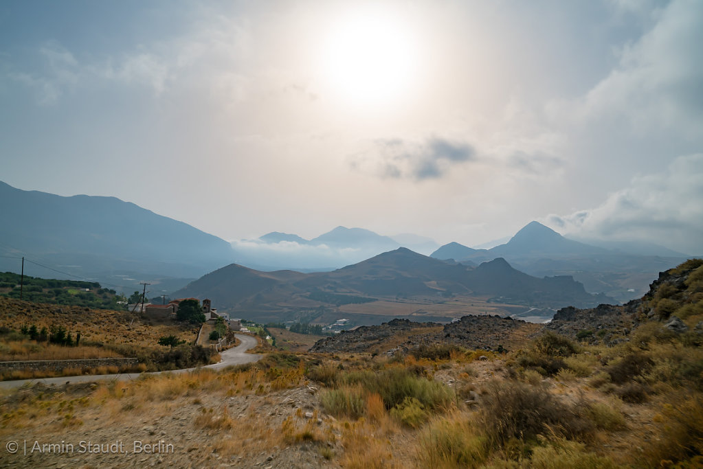 misty greek landscape with mountains and road