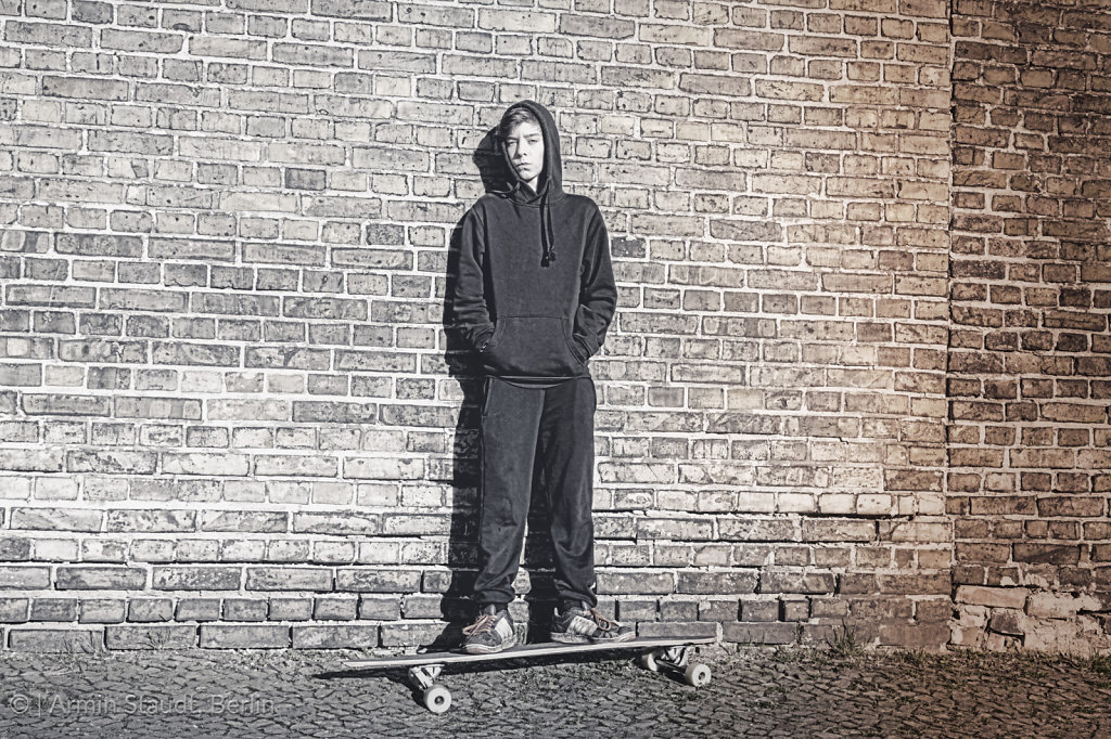 black and white shoot of a teenage boy with hoodie standing on a long board