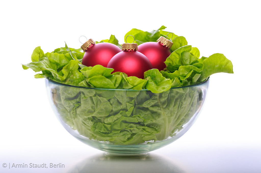 a bowl with fresh salad and three red christmas balls