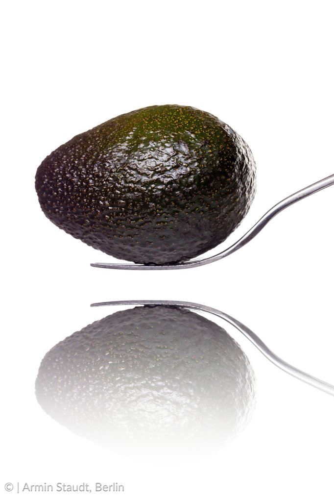an avocado laying on a fork with reflection, isolated on white