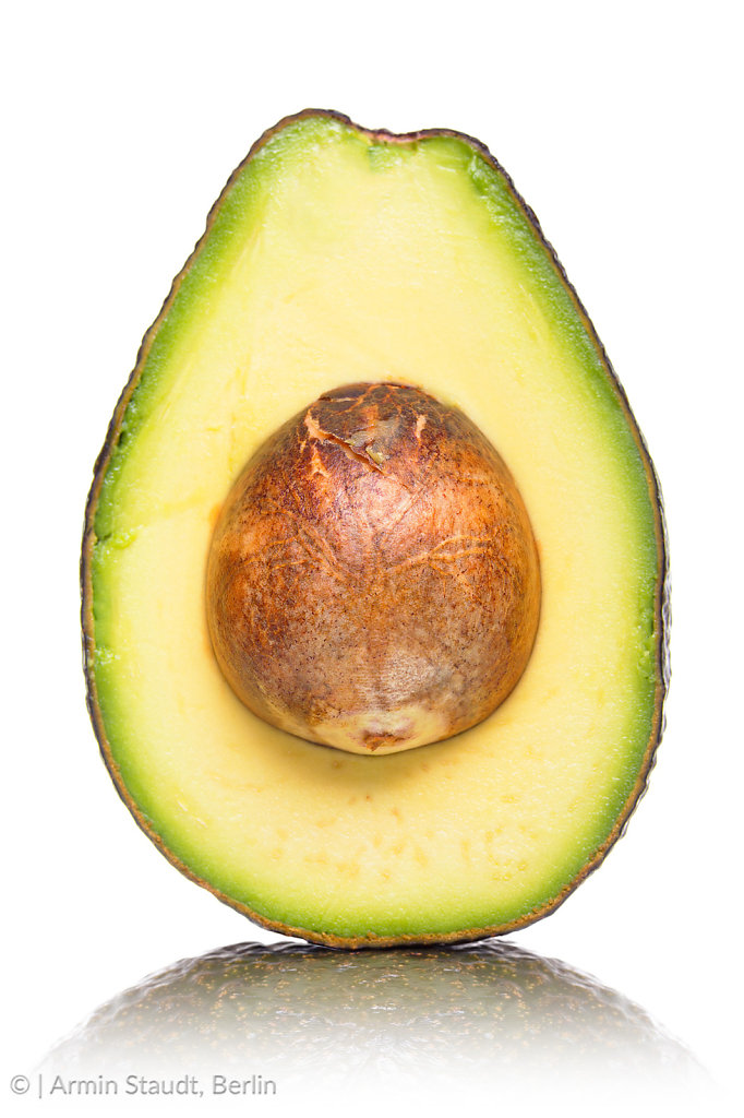 half of an avocado with kernel and reflection, isolated on white