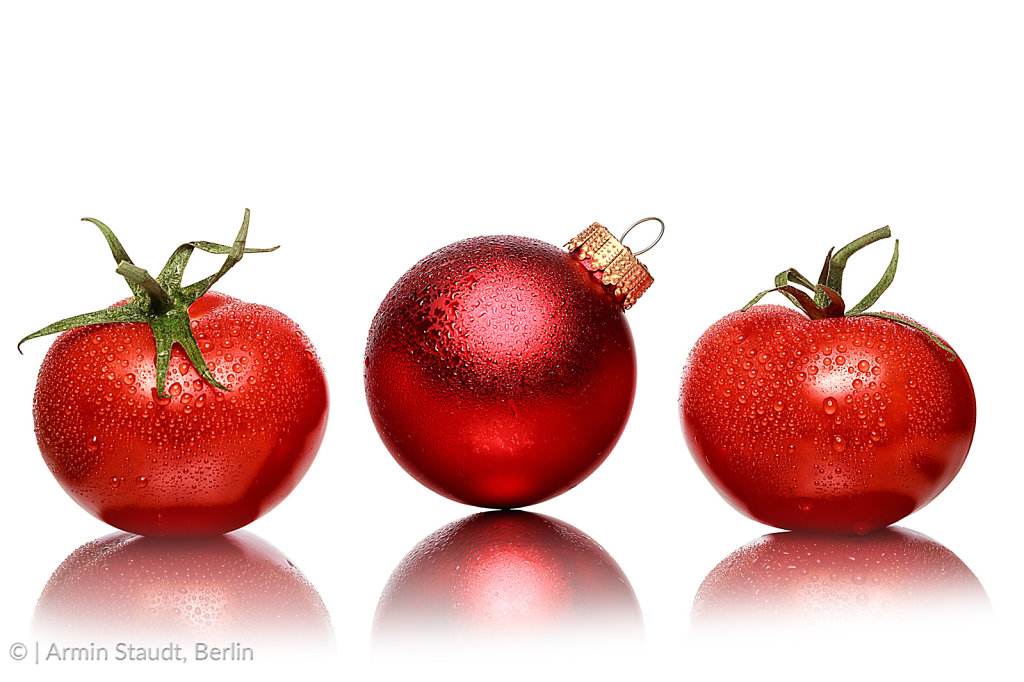 still life with two tomatoes and one red christmas ball, isolated on white