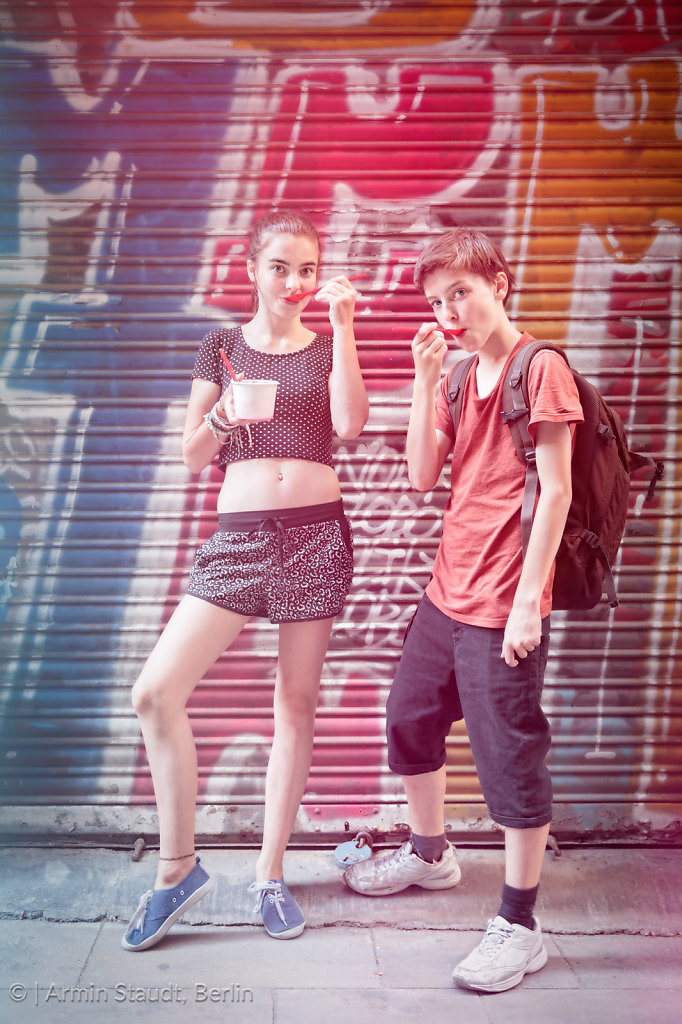 two teenager eating ice cream in front of a graffiti shutter