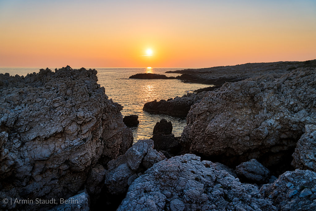mediterranean landscape, sunset over a stony shore