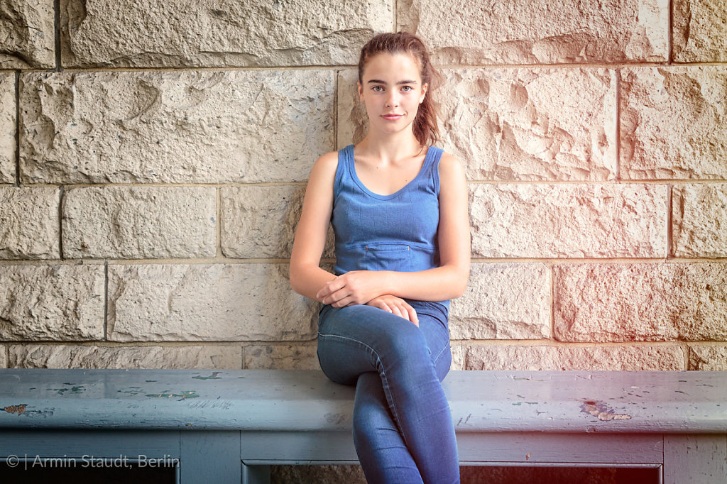 portrait of a beautiful teenage girl sitting on a wooden bench