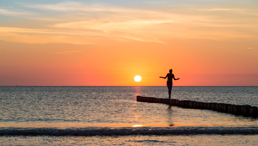 woman is balancing on a groin at sunset