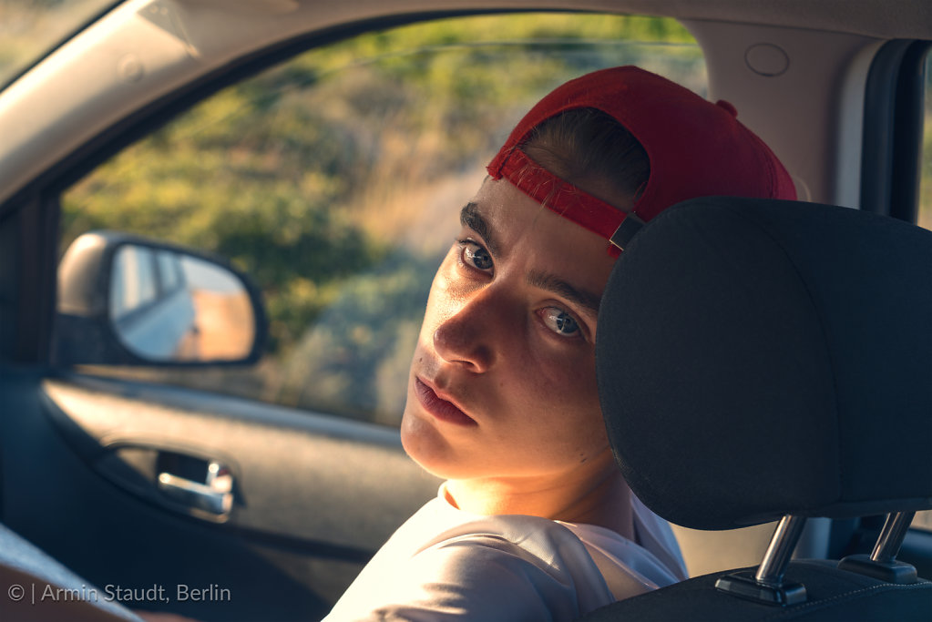 portrait of a young man, sitting in a car