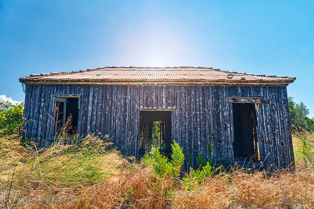 old abandoned wooden cottage with the sun behind