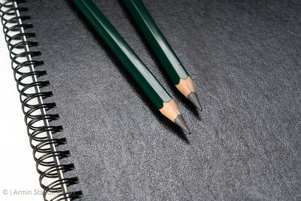 two green pencils laying on a black ring binder
